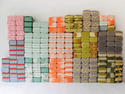 Textielkunst met gekleurde karakters van wollen dekens opgesteld als torens. Getiteld 'Geborgen Herinneringen' door Jeanne de Bie.