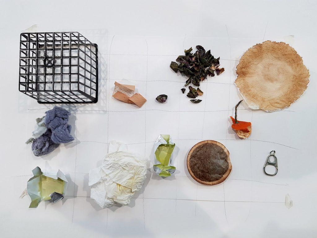 Een mandje, koffiepad, bliklipje, pleister en bouillonblokje. Proces van Fascinatie uit de afvalbak en overgang naar Pleister door Jeanne de Bie.