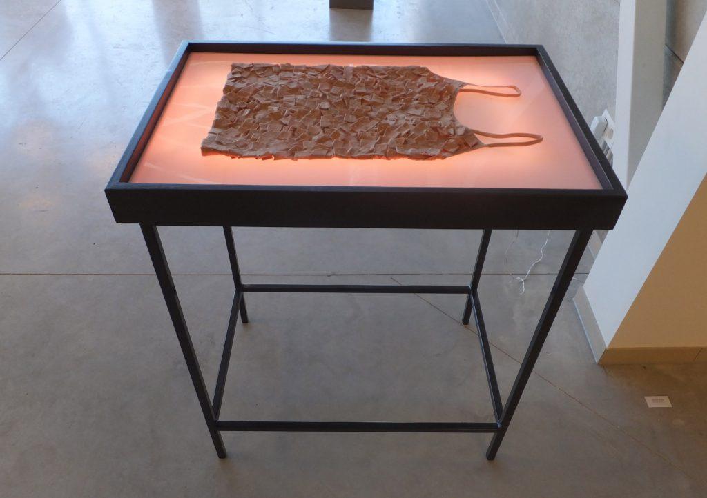 Hemdje van pleister (Plaster camisole) liggend op tafel met lichtbak als installatie door Jeanne de Bie, kunst over gezondheid, genezing en gewond zijn.