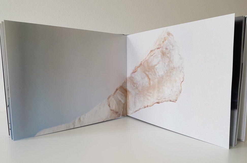 Boek met conceptuele textielkunst met het werk Rags of Light van Jeanne de Bie, van metaaldraad en wit vilt over vergankelijkheid.