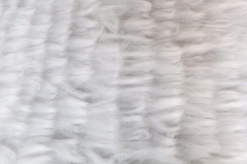 Bewogen beeld van wit vilt van boven, lichtinval als witte zee, beeldende kunst over vergankelijkheid door Jeanne de Bie genaamd Rags of light