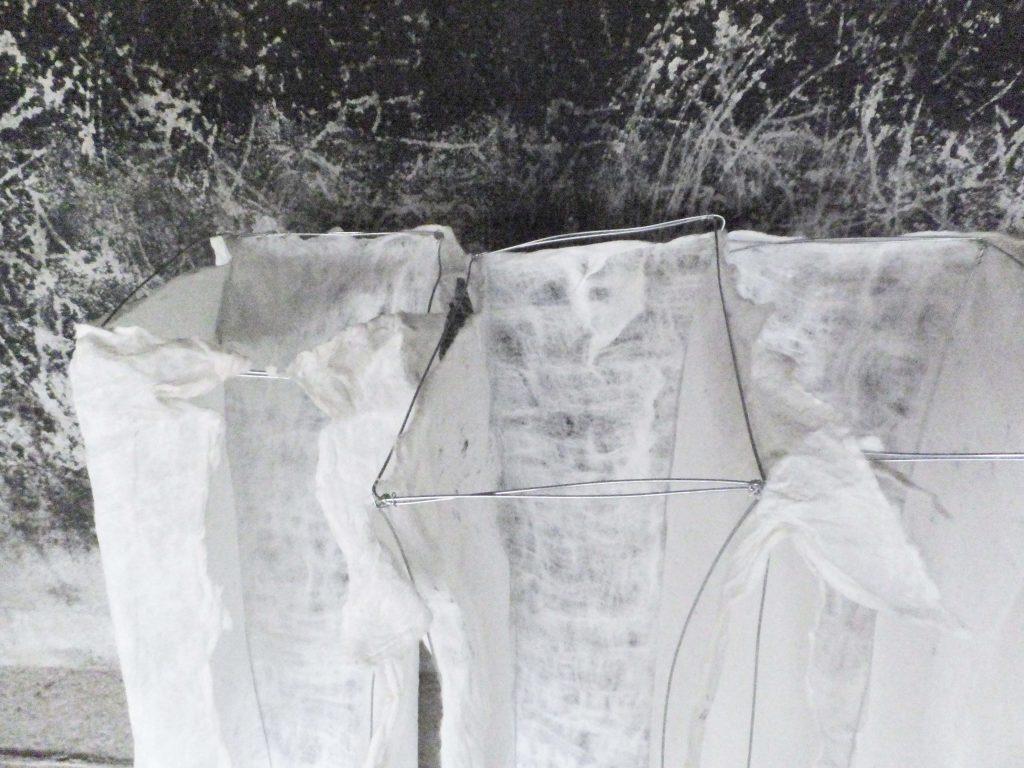 Kunstwerk (detail) van wit vilt en metaaldraad voor ruwe muur over vergankelijkheid, genaamd Rags of light. Textielkunst door Jeanne de Bie.