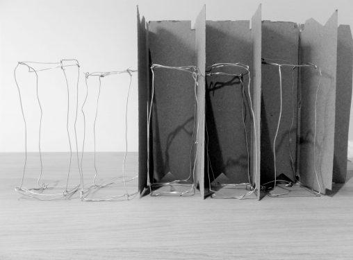 Draadwerken van metaal staand naast elkaar, deels in kleine ruimtes gepositioneerd. Zwart-wit. Kunstwerk door Jeanne de Bie, titel Rags of light.
