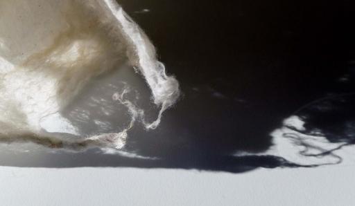 Close-up van zacht wit vilt, licht en donkere schaduw. Detail van het beeldende kunstwerk genaamd Rags of light (Vodden van licht) door Jeanne de Bie