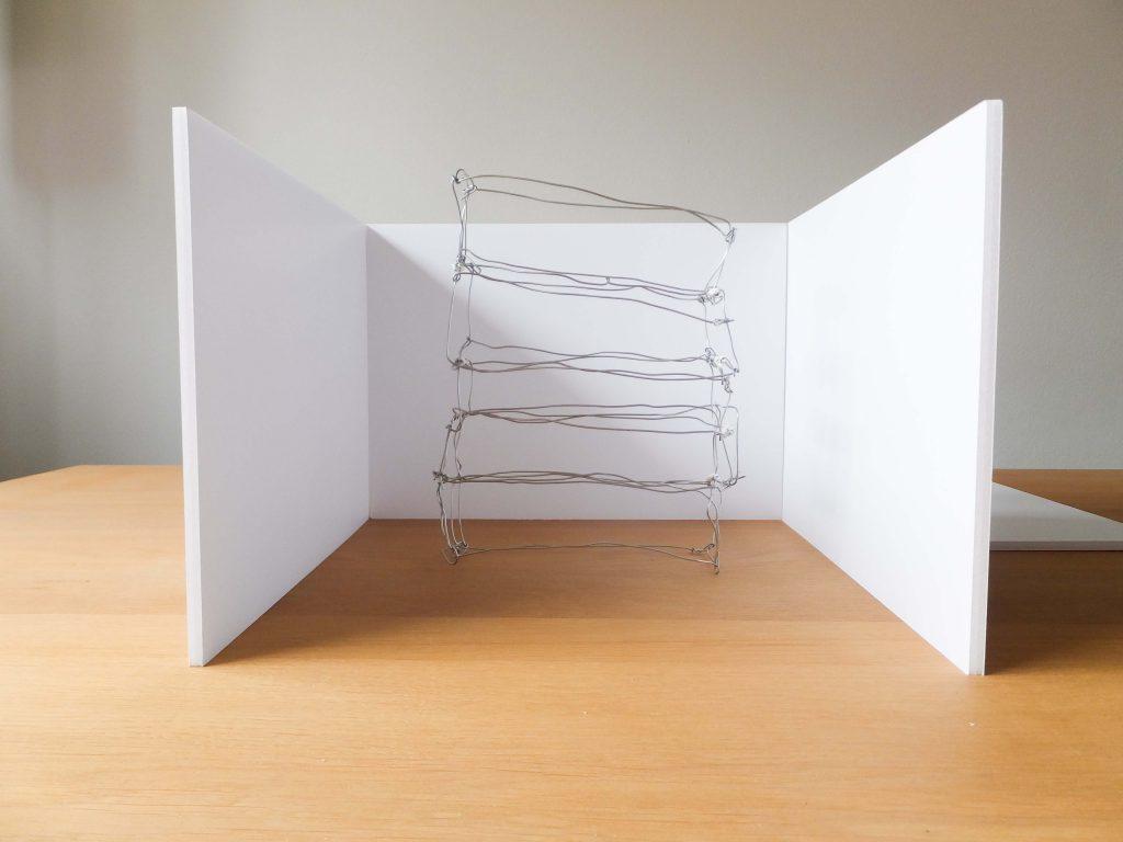 Draadwerk van metaal tussen witte muren met lichtinval van links, kleur. Beeldende kunst genaamd Rags of light (Vodden van licht) door Jeanne de Bie