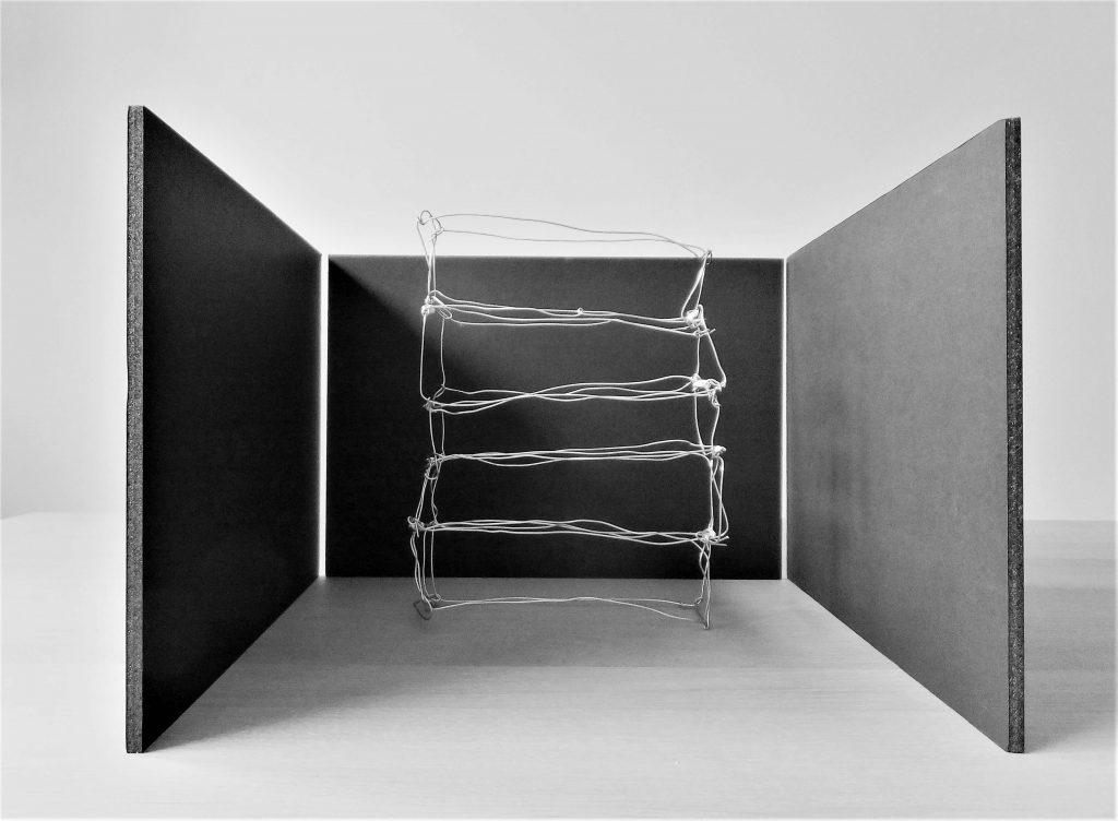 Draadwerk van metaal tussen donkere muren in lichte ruimte, zwart-wit en grijstinten. Beeldende kunst genaamd Rags of light door Jeanne de Bie.