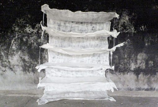 Kunstwerk van wit vilt en metaaldraad in lagen voor ruwe muur over vergankelijkheid, genaamd Rags of light. Textielkunst door Jeanne de Bie.