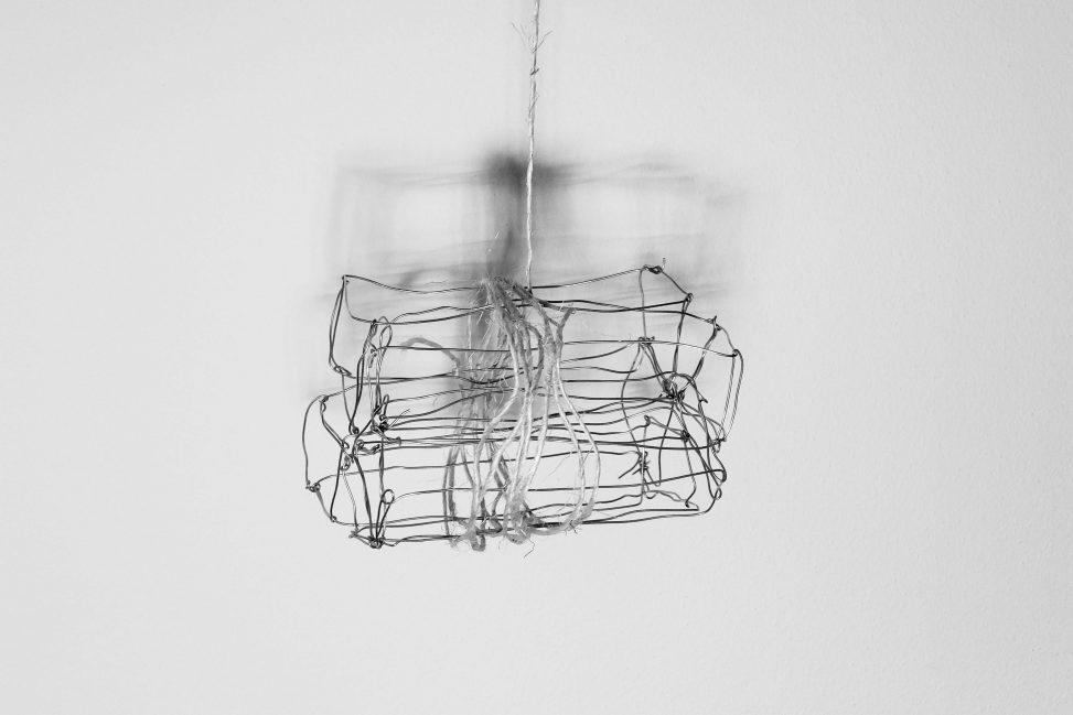 Draadwerk van metaal en touw met schaduw op muur. Kunst door Jeanne de Bie, werk genaamd: Rags of light (Vodden van licht), over vergankelijkheid.