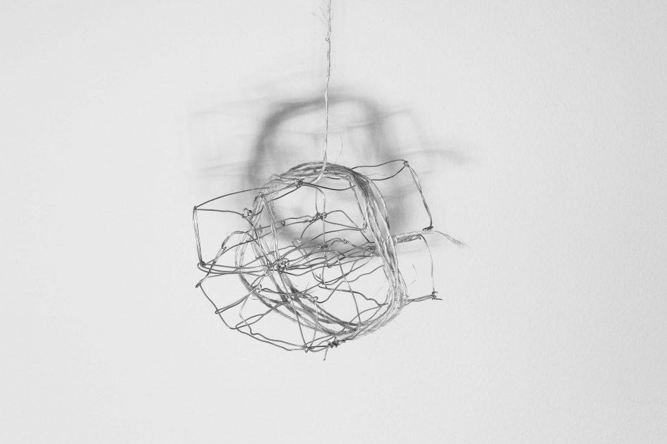 Draadwerk van metaal en touw met schaduw op muur. Kunst door Jeanne de Bie, werk genaamd: Rags of light (Vodden van licht) over vergankelijkheid.