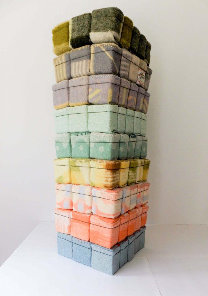 Textielkunst met gekleurde karakters van wollen dekens opgesteld als toren. Getiteld 'Geborgen Herinneringen' door Jeanne de Bie.