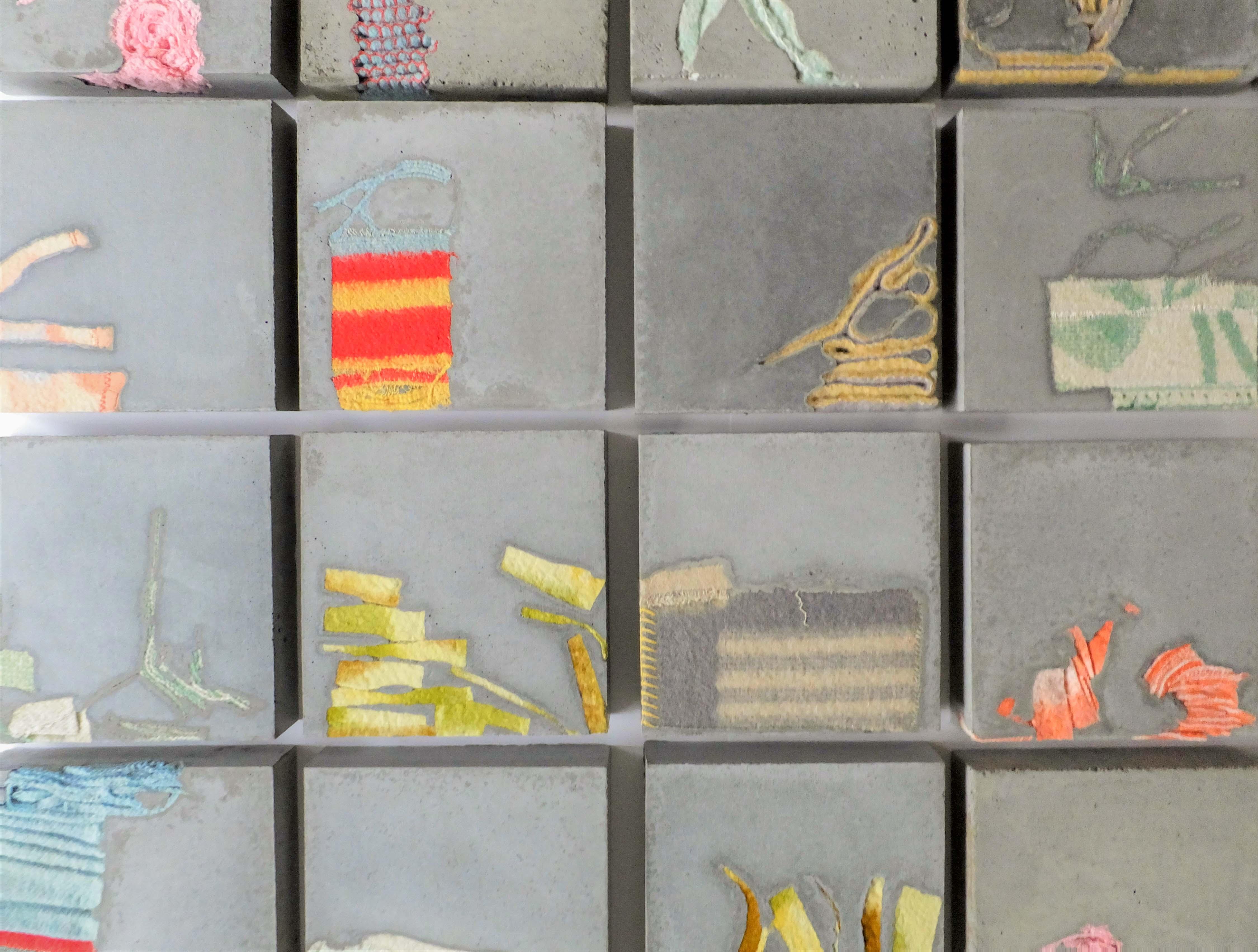 Installatie van vierkante karakters van cement met gekleurde dekens erin verweven. Textielkunst door Jeanne de Bie, genaamd Stil leven (Still life).