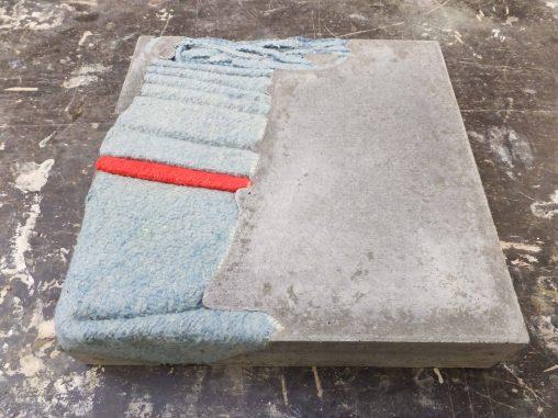 Vierkant karakter van cement met blauw met rode deken erin gegoten. Beeldende kunst genaamd Stil leven door Jeanne de Bie, inspiratie Wabi Sabi