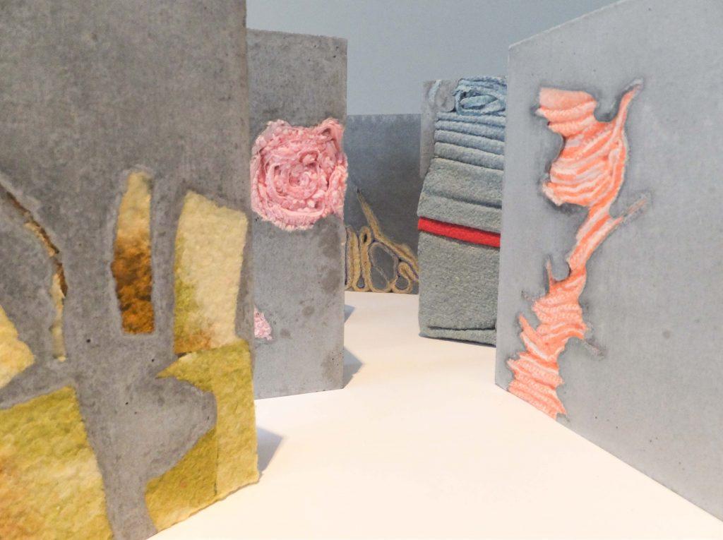 Vijf cementen vierkante karakters met blauw, roze en groene dekens verwerkt. Beeldende kunst: Stil leven door Jeanne de Bie, inspiratie Jeff Wall.
