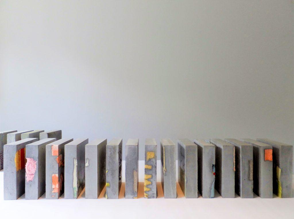 Rij betonnen vierkante karakters met gekleurde dekens verweven. Beeldende kunst: Stil leven door Jeanne de Bie, inspiratie Jeff Wall en Wabi Sabi.