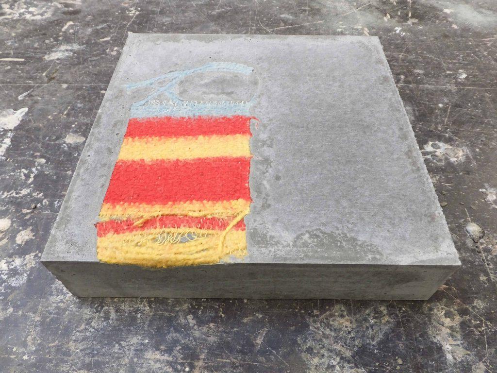 Vierkant karakter van cement met blauw, geel en rode deken erin gegoten. Beeldende kunst genaamd Stil leven door Jeanne de Bie, inspiratie Wabi Sabi