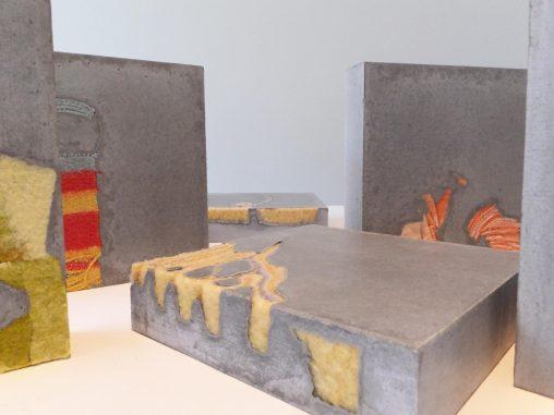 Vijf cementen vierkante karakters met gekleurde dekens erin verwerkt. Beeldende kunst: Stil leven door Jeanne de Bie, inspiratie Jeff Wall.